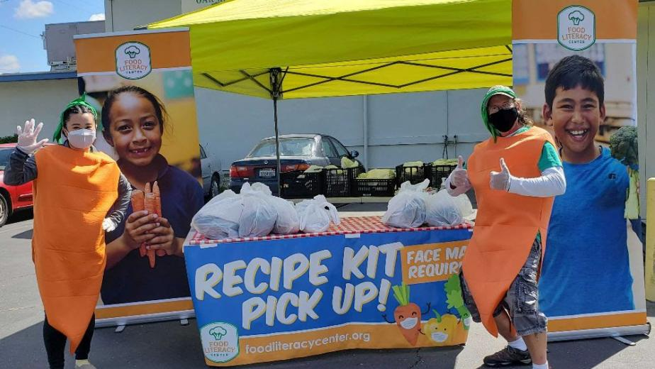 Employees in carrot costumes distributing recipe kits